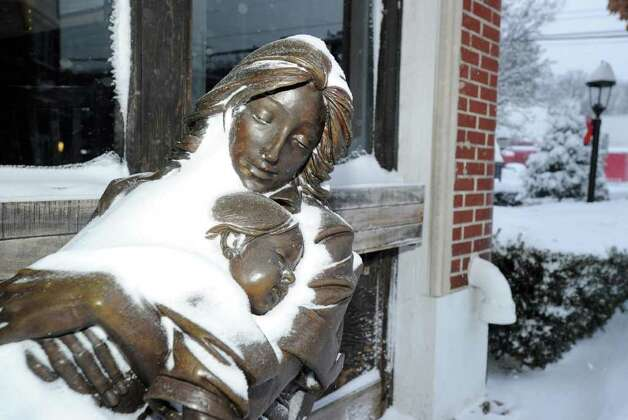 A snow-covered statue at the bottom of Greenwich Avenue, Wednesday morning, Jan. 12, 2011. Photo: Bob Luckey / Greenwich Time
