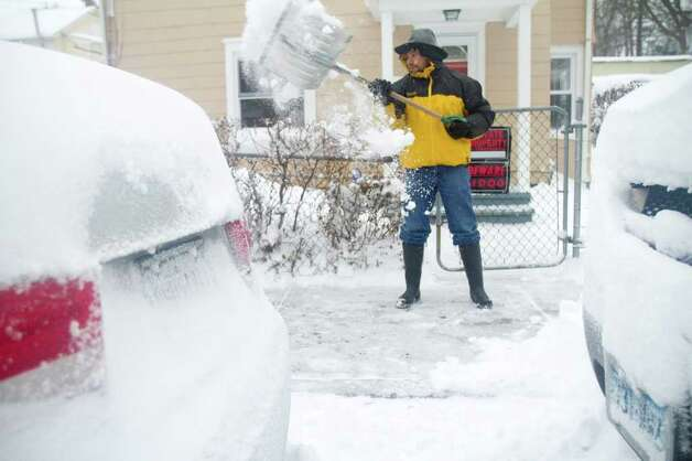 Rapael Bejarano shovels snow during a snow storm in Stamford, Conn. on Tuesday, Jan. 12, 2011. Photo: Contributed Photo / Stamford Advocate Contributed
