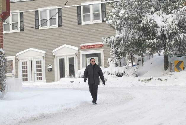 A pedestrian walks down a snow-covered Hamilton Avenue, Chickahominy, Wednesday morning, Jan. 12, 2011. Photo: Bob Luckey / Greenwich Time