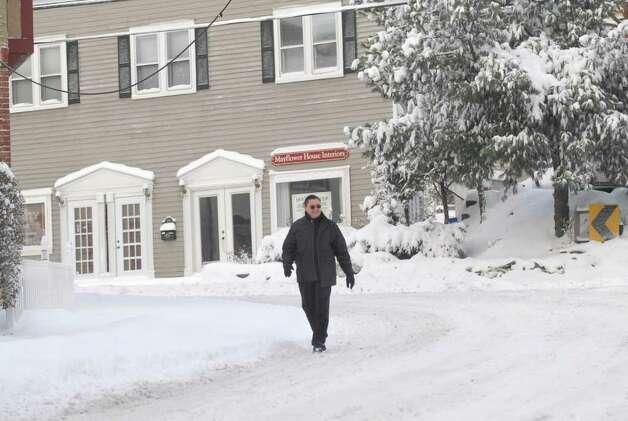 A pedestrian walks down a snow-covered Hamilton Avenue, Chickahominy, Wednesday morning, Jan. 12, 2011. Photo: Bob Luckey / Greenwich Time