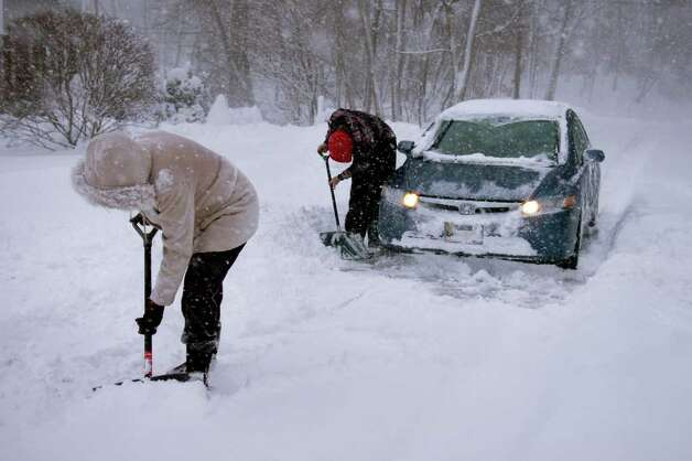 Linda Peckoraro and Ian Cunningham work to move snow in front of Cunningham's car stuck on Pumpkinground Rd. in Stratford, Conn. Wednesday, Jan. 12th, 2011. Photo: Ned Gerard / Connecticut Post