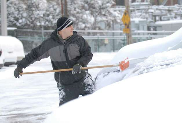 Chris Carrea clears snow off of cars at the Lexus dealership on Railroad Avenue, Greenwich, Wednesday morning, Jan. 12, 2011. Photo: Bob Luckey / Greenwich Time