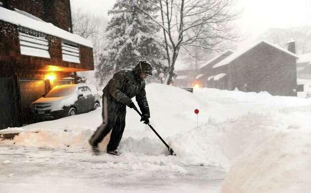 William Rivera shovels the snow in front of his condo at Shepherd Hill in Danbury early Wednesday morning, January 12, 2010. Photo: Carol Kaliff / The News-Times