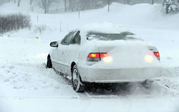 A car, stuck in the snow on Federal Road in Danbury Monday morning, spins its wheels. Photo taken Wednesday, January 12, 2011. Photo: Carol Kaliff / The News-Times