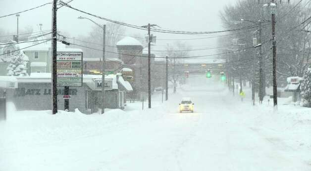 A lone car travels on White Street in Danbury Wednesday morning. A reported 15 to 20 inches of snow fell in the Greater Danbury area. Photo taken Wednesday, January 12, 2011. Photo: Carol Kaliff / The News-Times