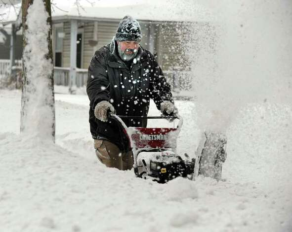 Jim Hinckley snow blows his walkway on Locust Avenue in Danbury early Wednesday morning, January 12, 2011. Photo: Carol Kaliff / The News-Times