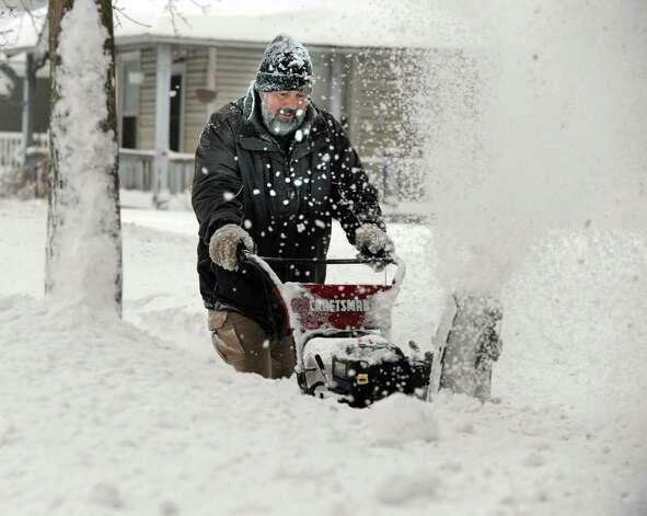 Jim Hinckley snow blows his walkway on Locust Avenue in Danbury early Wednesday morning, January 12, 2011. Photo: Carol Kaliff / The News-Times