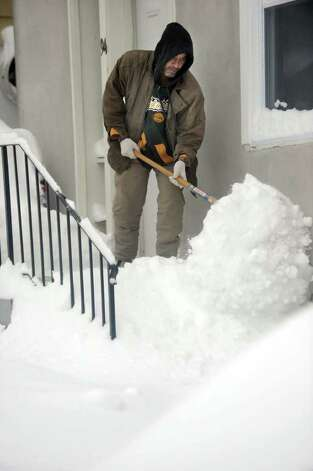 A man named Ivani, shovels the snow from his steps on Town Hill Avenue in Danbury Wednesday morning, January 12, 2011. Photo: Carol Kaliff / The News-Times