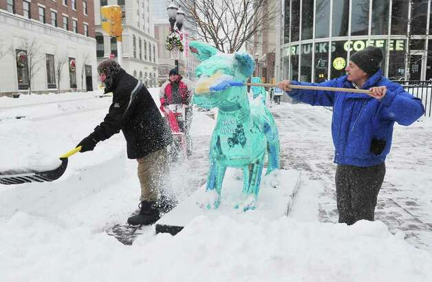 A group of men clear the sidewalk, and shovel off the statue, outside the Ferguson Library in Stamford, Conn. on Tuesday, Jan. 12, 2011. Photo: Kathleen O'Rourke / Stamford Advocate