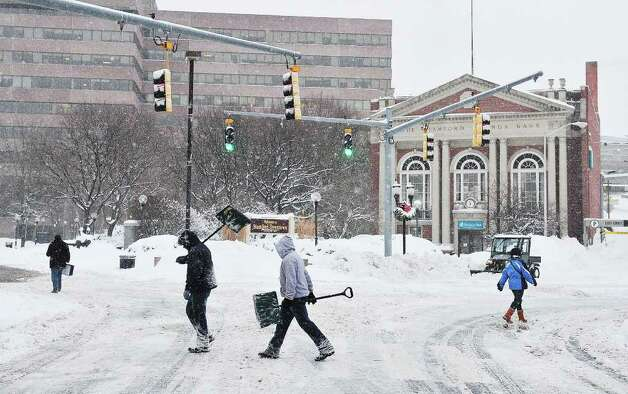 Pedestrians and plows occupied the streets this morning in downtown Stamford on Tuesday, Jan. 12, 2011. Photo: Kathleen O'Rourke / Stamford Advocate