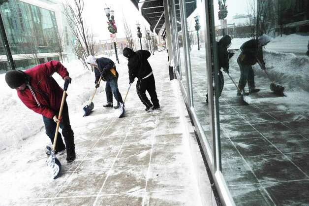 Men shovel the sidewalk outside Target as snow continued to fall in Stamford, Conn. on Tuesday, Jan. 12, 2011. Photo: Kathleen O'Rourke / Stamford Advocate