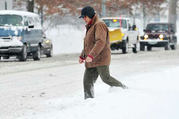 A pedestrian walks down an unplowed sidewalk in downtown Stamford on Tuesday, Jan. 12, 2011. Photo: Kathleen O'Rourke / Stamford Advocate