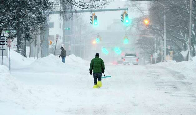 A man walks down Summer Street with shovel in hand as snow continued to fall this morning in Stamford, Conn. on Tuesday, Jan. 12, 2011. Photo: Kathleen O'Rourke / Stamford Advocate