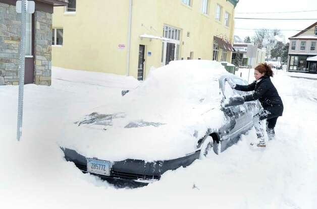 Alexandra Ochoa of Byram clears snow from her car that was parked on Henry Street, Wednesday morning, Jan. 12, 2011. Photo: Bob Luckey / Greenwich Time