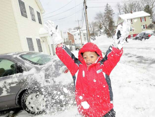 Anthony Colmenares, 3, of Byram, enjoys the snow by throwing it in the air outside of his home, Wednesday morning, Jan. 12, 2011. Photo: Bob Luckey / Greenwich Time