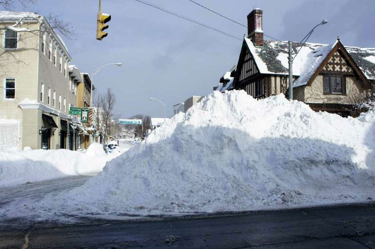 A towering pile of snow stands at the intersection of Post Road East and Main Street in Westport on Wednesday morning, after plows cleared snow to the side of the normally busy corner.