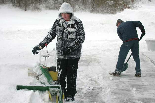 Evan Conway and his dad, Tom, clear the lot at their service station, Conway's Irving on Black Rock Turnpike in Fairfield, Conn. on Wednesday Jan. 12, 2011. Photo: Cathy Zuraw / Connecticut Post