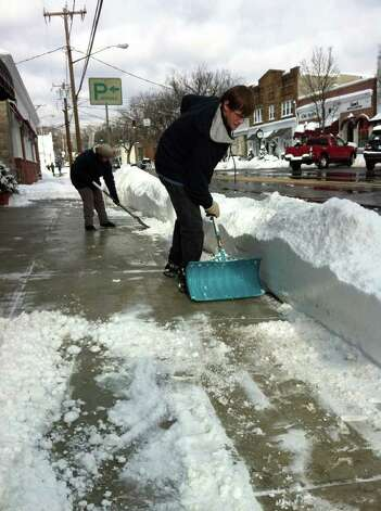 "Tommy Brown, 19, and his mother Janet shovel snow in front of 239 Sound Beach Ave. in Old Greenwich Wednesday morning. Tommy's father, Robert, not in photo, said it got harder to shovel as the sun came up because it melted the snow and made it heavier. ""The snowblower gets clogged and it doesn't blow the snow as well,"" he said. Photo: Francis MacEachern / Greenwich Time"