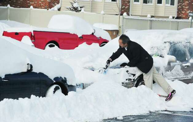 John Ramos shovels off his car after snow blankets the area in Stamford, Conn. on Wednesday January 12, 2011. Photo: Kathleen O'Rourke, Stamford Advocate / Stamford Advocate