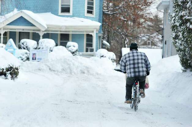 A man finds rides his bike along Summer Street as snow blankets the area in Stamford, Conn. on Wednesday January 12, 2011. Photo: Kathleen O'Rourke, Stamford Advocate / Stamford Advocate