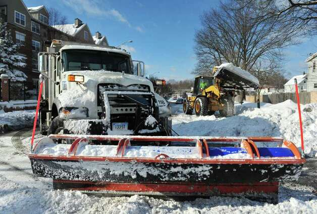 City crews plow and remove snow from intersections after snow blankets the area in Stamford, Conn. on Wednesday January 12, 2011. Photo: Kathleen O'Rourke, Stamford Advocate / Stamford Advocate