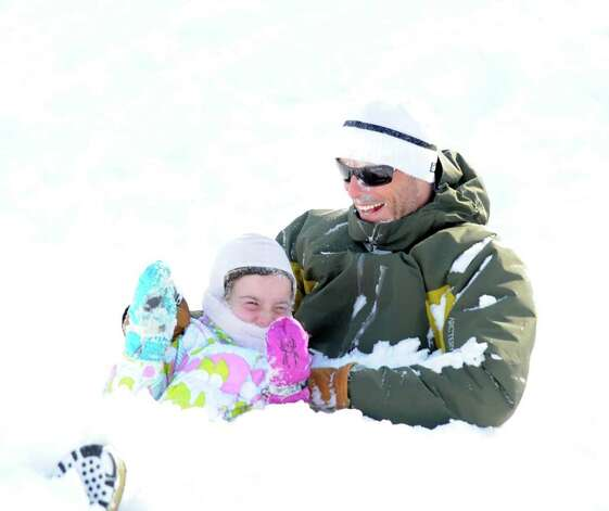Greenwich resident Tony Howell and his daughter, Brooke, 7, react after getting blasted with some snow while sledding in virgin powder on the hill next to the Westrn Greenwich Civic Center, Wednesday, Jan. 12, 2011. Photo: Bob Luckey / Greenwich Time