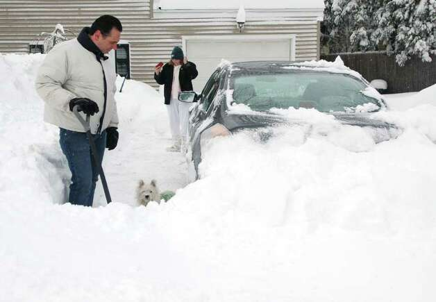 Paul Arancio and Linda Stanton clear a path for Mac, a Westie dog that is anxious to get out of the driveway on Pansy Rd.in Fairfield, Conn. on Wednesday Jan. 12, 2011. Photo: Cathy Zuraw / Connecticut Post