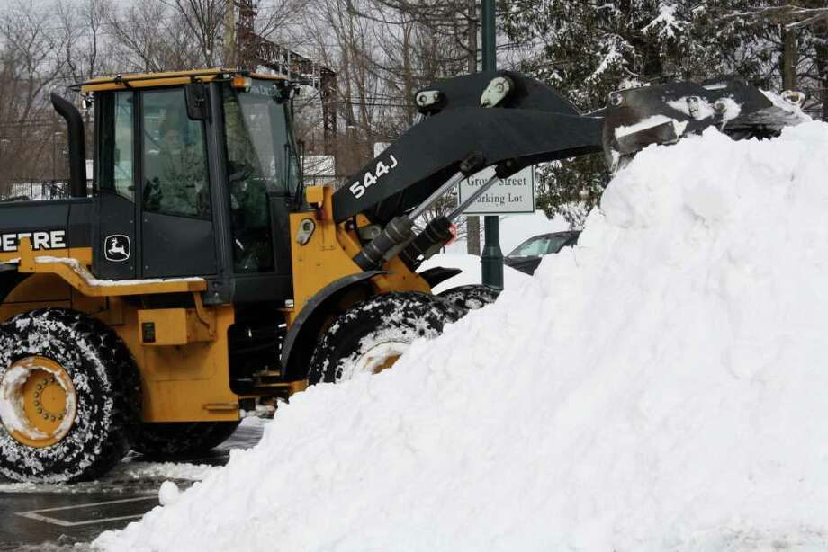 Crews were out on the streets and in the parking lots clearing the 18 inches of snow that hammered the town Tuesday night into Wednesday. Photo: Contributed Photo / Darien News