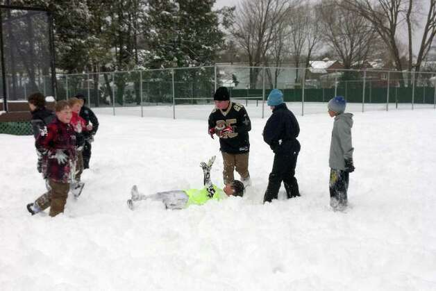"Wednesday's snowstorm close Greenwich schools but not football. Naoya Fukuchi, 13, on ground hands the football to Brendan Norberto, 14, after he was tackled during a game at Loughlin Avenue Park in Cos Cob. Also playing were twins Trevor and Colin Ingraham, Brandon Aguda, Matt Lamanna, Steven Gil, and Jack Freiheit. They all live in Cos Cob and all go to Central Middle School except Norberto who attends Greenwich High School. ""This is fine you can dive in it,""  Trevor Ingraham said. ""And you don't get hurt,"" Norberto added. Photo: Francis MacEachern / Greenwich Time"