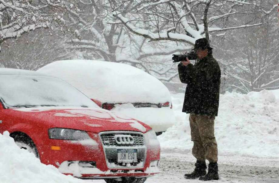 Times Union Staff Photographer John Carl D'Annibale takes aim on a potential weather photograph across from the Capitol in Albany on Wednesday, Jan. 12, 2011.( Michael P. Farrell/Times Union ) Photo: Michael P. Farrell