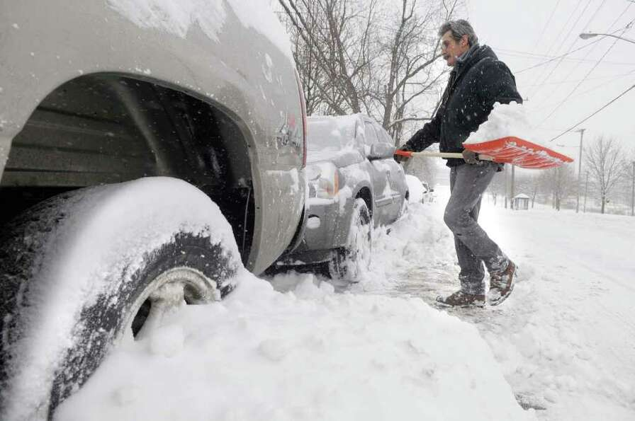 Glen Moir digs out his vehicle from the snow pushed up by plows in Rensselaer on Wednesday, Jan. 12,