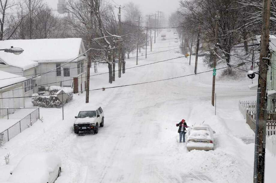 Cindy Cafaro cleans off the snow from her car outside in Rensselaer on Wednesday, Jan. 12, 2011.  (Paul Buckowski / Times Union) Photo: Paul Buckowski / 10011727A