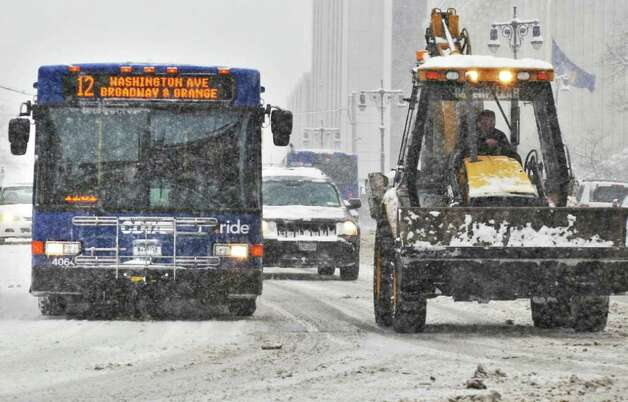 Snow removal equipment shares the road with Capital District Transportation Authority buses in Albany on Wednesday,  Jan. 12, 2011.   (John Carl D'Annibale / Times Union) Photo: John Carl D'Annibale / 10011727A