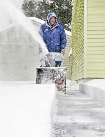John Ropelewski uses a snowblower to clear the driveway of his home in Colonie on Wednesday, Jan. 12, 2011.   (John Carl D'Annibale / Times Union) Photo: John Carl D'Annibale / 10011727A