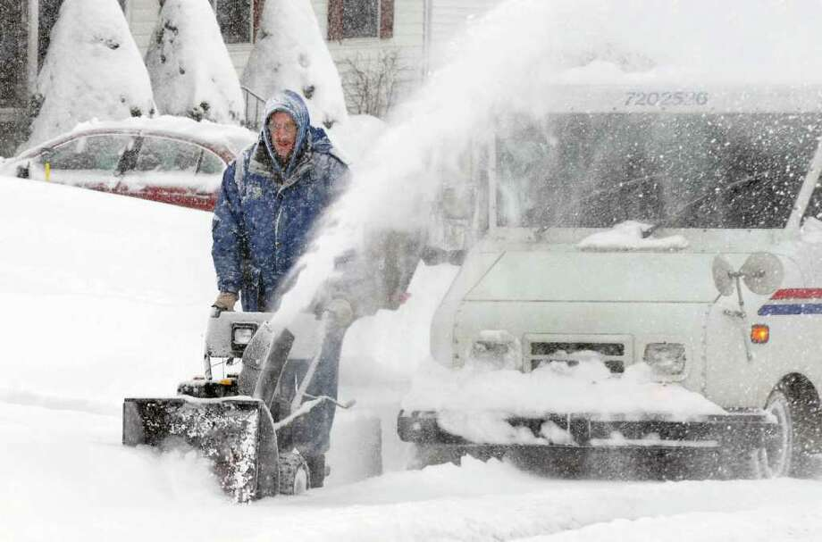John Ropelewski uses a snowblower to clear in front of his home in Colonie Wednesday, Jan. 12, 2011.   (John Carl D'Annibale / Times Union) Photo: John Carl D'Annibale / 10011727A