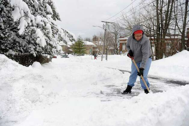 Laurah Hardy shovels the street beyond her driveway on Hillside Street in Norwalk on Wednesday, January 12, 2011. Photo: Lindsay Niegelberg / Connecticut Post