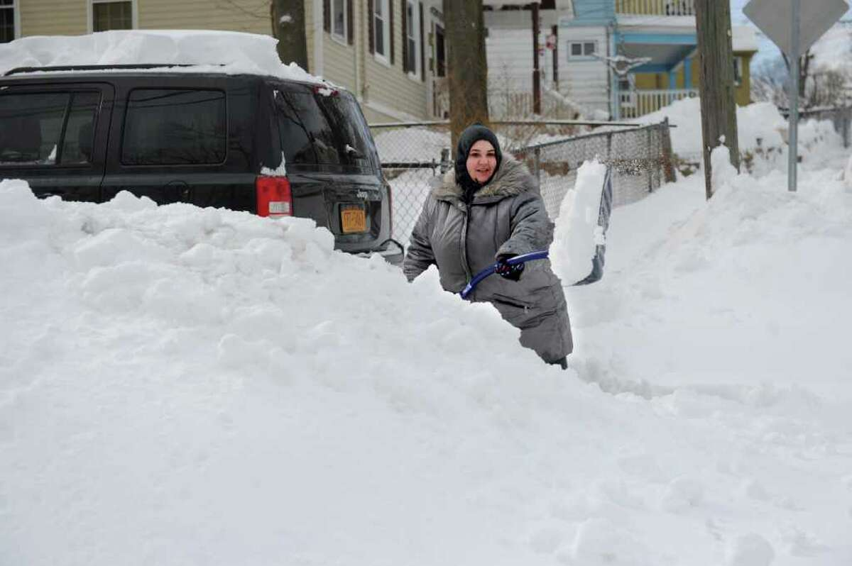 Jodi DellaVentora is nearly hidden behind the pile of snow she grows as she shovels her driveway on Hillside Street in Norwalk on Wednesday, January 12, 2011.