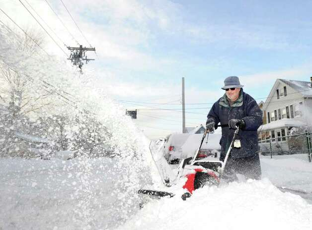 Joe Mancusi uses his snow-blower to clear a neighbor's driveway during the aftermath of the snowstorm, Wednesday morning, on Hamilton Avenue, Chickahominy, Wednesday, Jan. 12, 2011. Photo: Bob Luckey / Greenwich Time