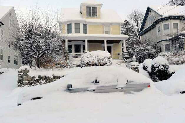 A car almost completely covered in snow on Lincoln Avenue, Greenwich, during the aftermath of snowstrom, Wednesday morning, Jan. 12, 2011. Photo: Bob Luckey / Greenwich Time