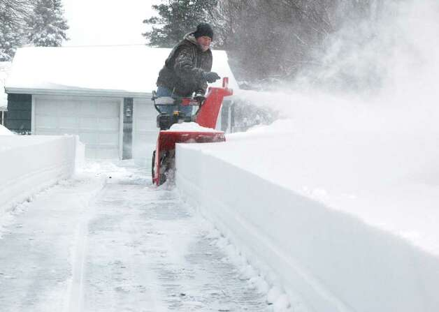 Mark Morehouse adjusts his snowblower as the wind blows the snow around his Judd St. driveway in Fairfield, Conn. on Wednesday Jan. 12, 2011. Photo: Cathy Zuraw / Connecticut Post