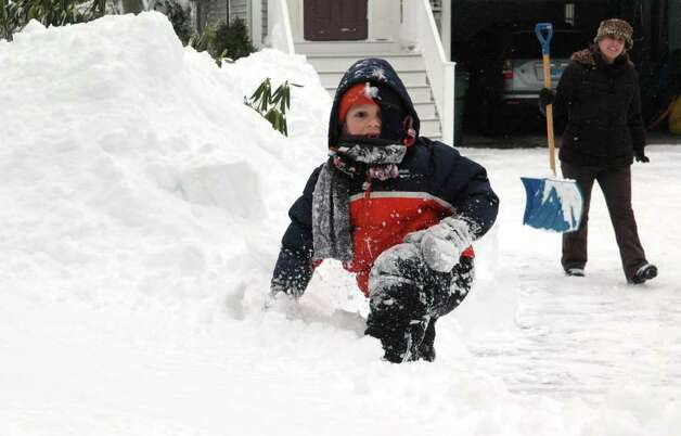 6 year-old Dylan Field climbs the snow pile in his Pansy Road yard in Fairfield, Conn. on Wednesday Jan. 12, 2011. Dylan's mom, Rosemary, kept a close eye out while continuing to clear the driveway after more than a foot of snow fell on the area. Photo: Cathy Zuraw / Connecticut Post
