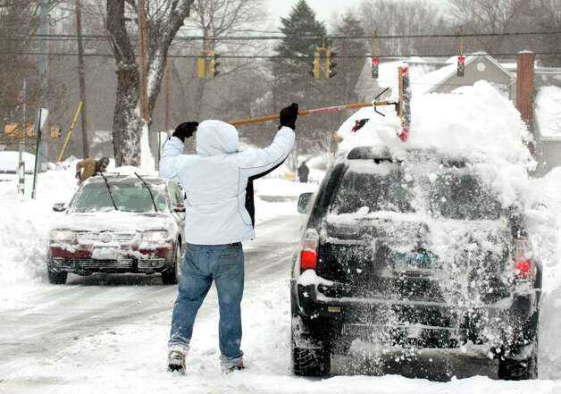 Slawek Wierzgacz cleans off the top of his car after pulling out of his Pansy Rd. driveway in Fairfield, Conn. on Wednesday, Jan. 12, 2011. Photo: Cathy Zuraw / Connecticut Post