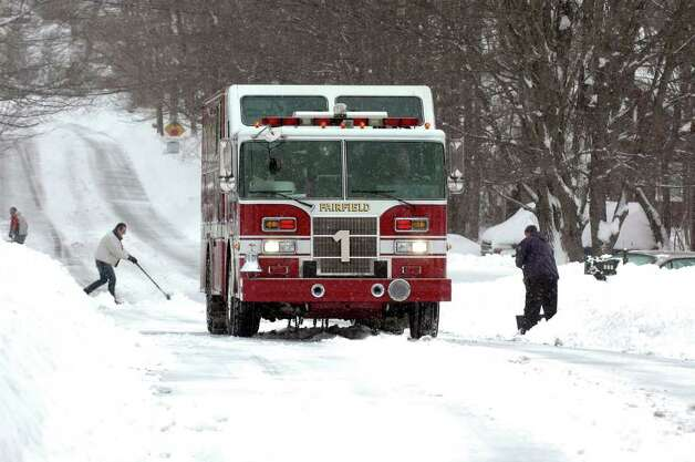 A firetruck heads down Pansey Rd. in Fairfield, Conn. as resident clear their driveways on Wednesday, Jan. 12, 2011. Photo: Cathy Zuraw / Connecticut Post
