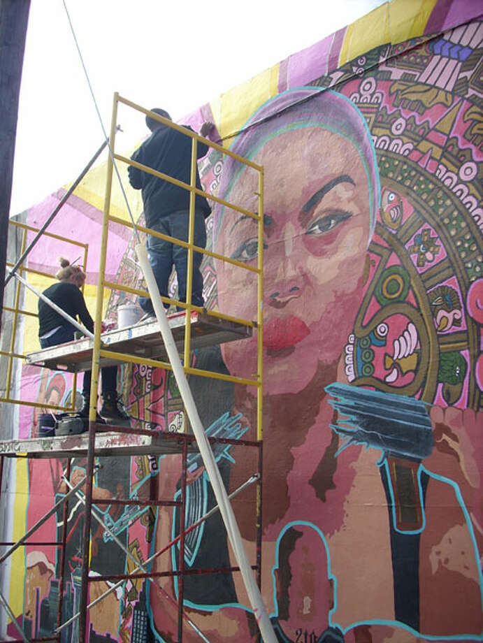 "Ruth Buentello, left and John Montez work on ""End Barrio Warfare,"" located at 1401 S. Brazos St. It will be unveiled Jan. 22.Photo by Noi Mahoney"