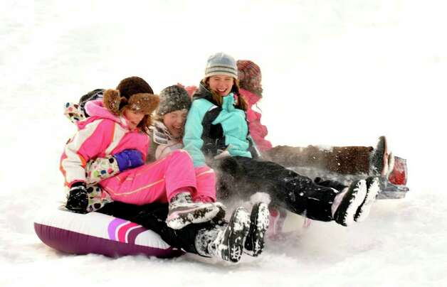 Lauren Gherna, 9, left, Jamie Gherna, 12, and Sarah Baker, 13, right, all of Danbury, sled at Richter Park in Danbury, Wednesday, Jan. 12, 2010. Photo: Michael Duffy / The News-Times