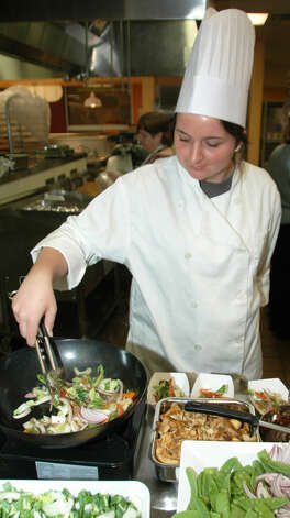 Smithson Valley High student Amy Baker shows her stir-frying expertise as she and other aspiring chefs learn the best way to preserve nutrients in their food.