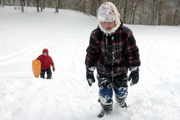 Tyler Eklund (front) and his brother Anthony Eklund climb back up the hill while sledding in Boothe Memorial Park in Stratford, Conn. Wednesday, Jan. 12th, 2011. Photo: Ned Gerard / Connecticut Post