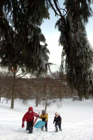 Anthony Eklund, Josh Duffy and Tyler Eklund climb back up the hill while sledding in Boothe Memorial Park in Stratford, Conn. Wednesday Jan. 12th, 2011. Photo: Ned Gerard / Connecticut Post