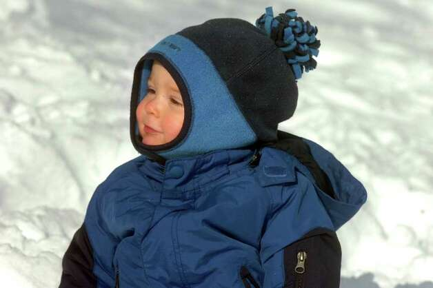 Harrison Mara, 1, watches sledders along East Parkway in Stratford, Conn. Wednesday, Jan. 12th, 2011. Photo: Ned Gerard / Connecticut Post