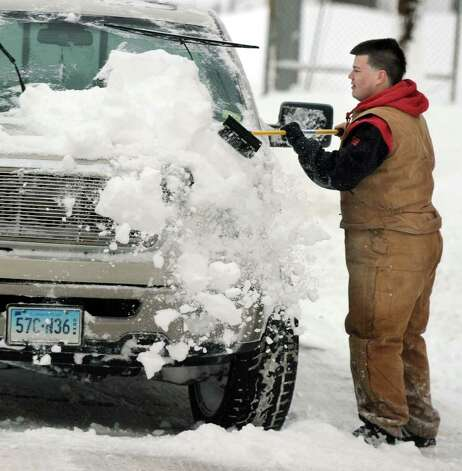 Ed Oliveira clears the snow from the front of his truck on Nichols Street in Danbury late Wednesday morning, January 12, 2011. Photo: Carol Kaliff / The News-Times